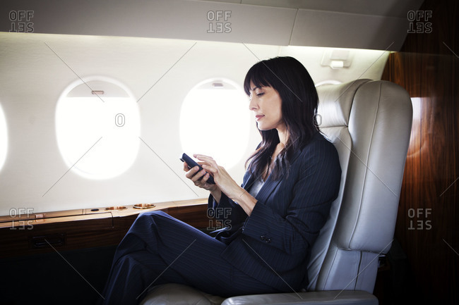 Businesswoman looking at her smartphone on a private jet