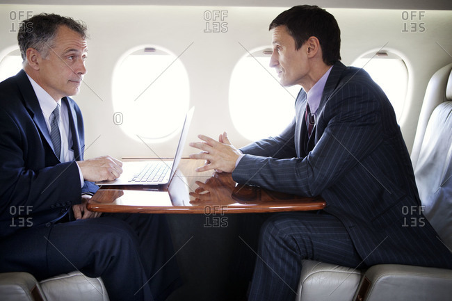 Businessmen having a discussion on a private jet
