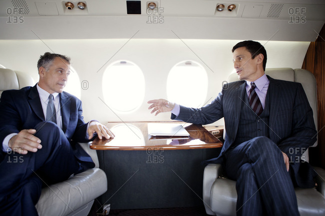 Businessmen talking on a private jet