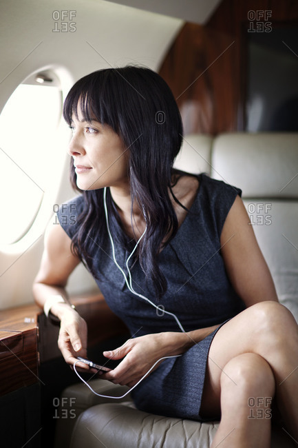 Businesswoman listening to music on a private jet