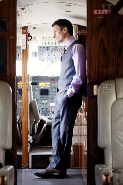 Businessman standing at the cockpit of a private jet