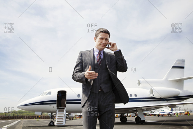 Businessman talking on the phone at the Laguardia airport, NYC, USA