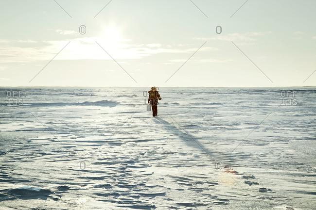 Ice fisher walking in rural Alaska