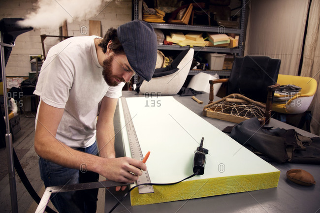 Designer measuring a piece of wood in a workshop