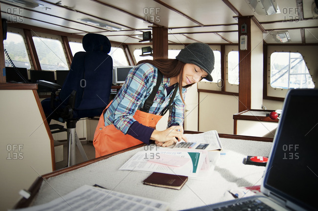 Young woman using a calculator on a boat