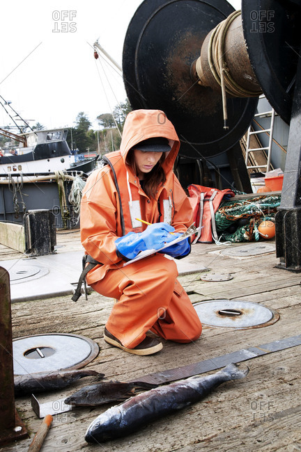 Woman measuring a fish on a boat