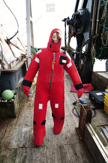 Woman wearing a neoprene survival suit on a boat