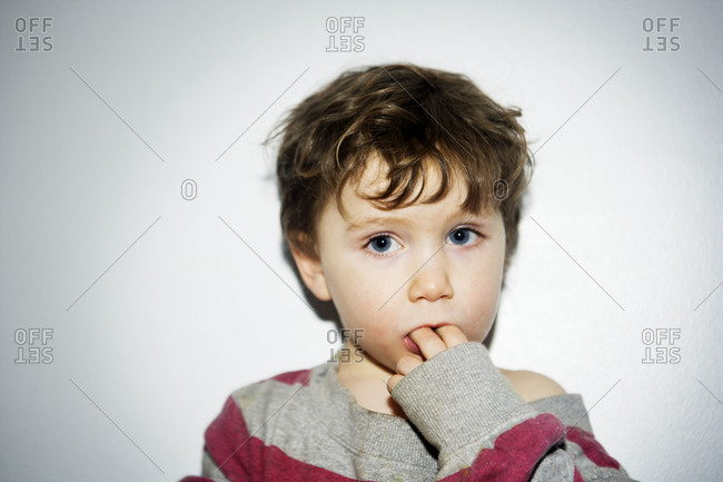 Young boy chewing on his fingers