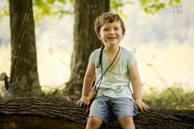Boy sitting on a tree trunk smiling
