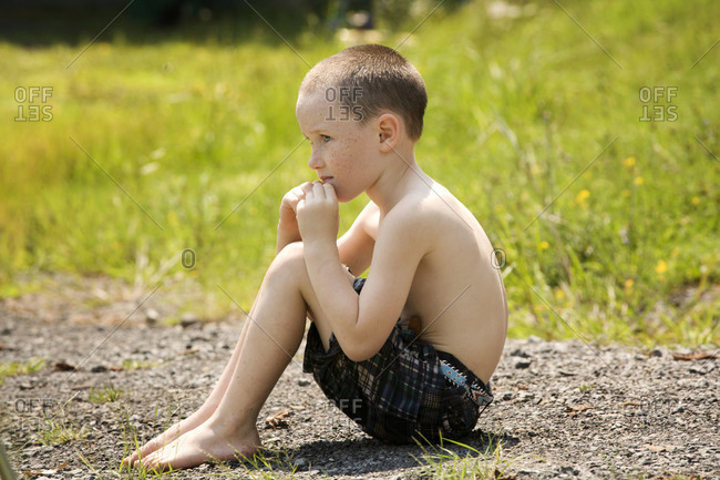 Boy sitting on the ground outdoors