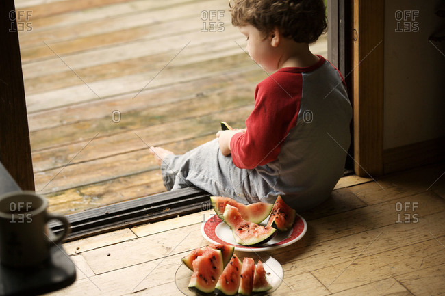 Young child sitting in the door with slices of watermelon