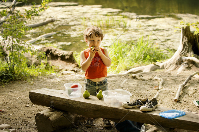 Boy eating a pear outdoors
