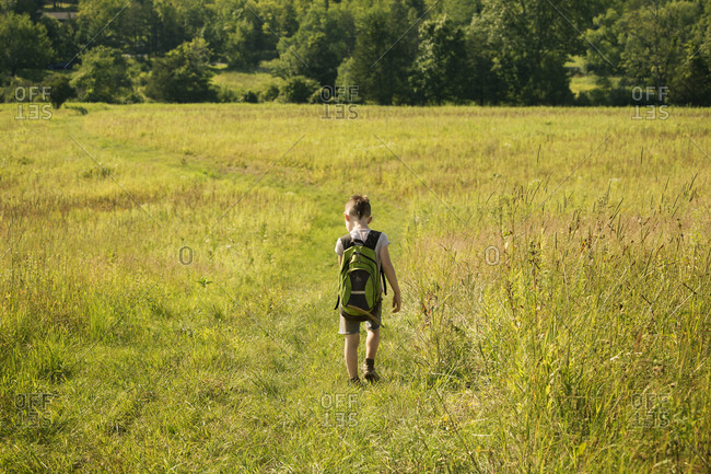 Boy walking on a field with backpack