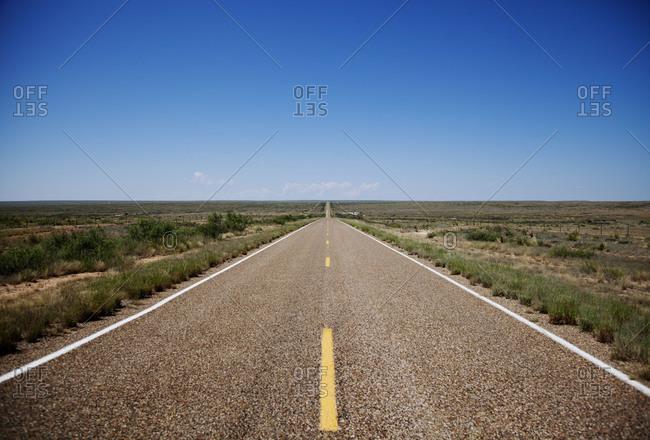 Empty road crossing a plain