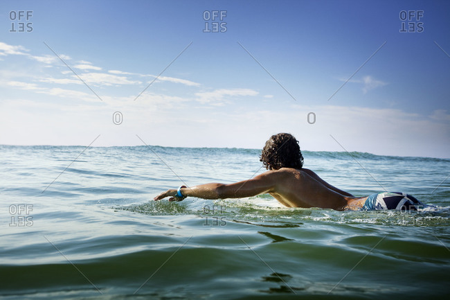 Man paddling on surfboard in the sea