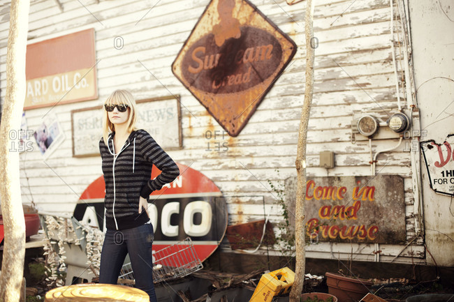 Young woman standing next to old signs