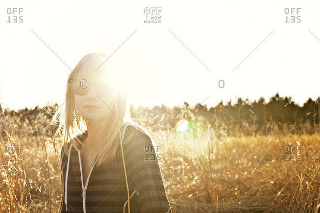 Young woman standing on a field at sunset