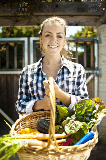 Woman holding basket with fresh vegetables