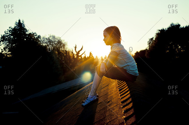 Young girl sitting on the roof