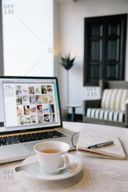 Laptop near tea and notepad
