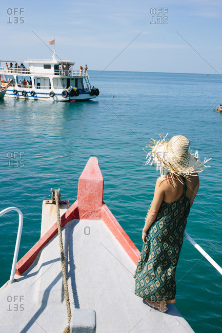 Woman on front of boat looking at sea ferry