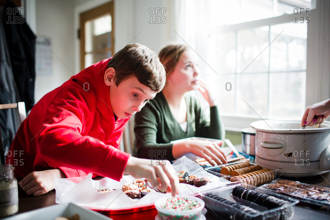 Boy grabbing sprinkles during dessert preparation