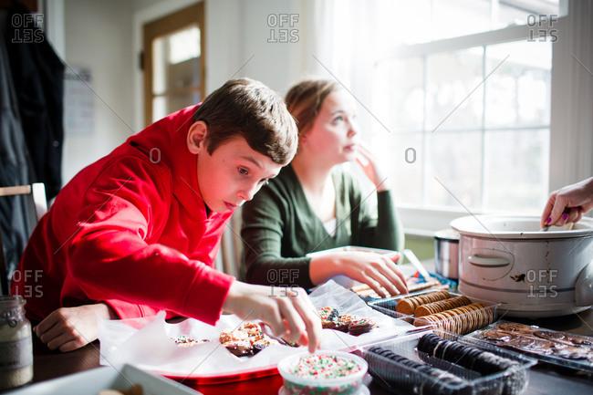 Boy grabbing sprinkles during dessert preparation