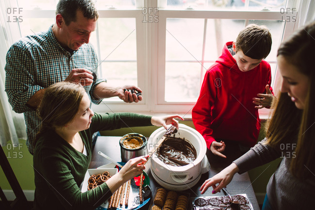 Family dipping treats in chocolate