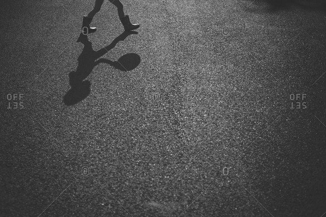 Legs and shadow of child with ball