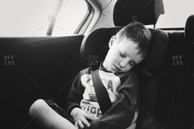 Boy fast asleep in car seat