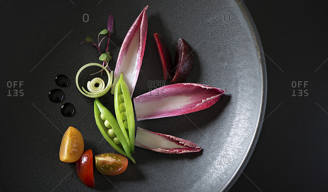 Fine dining salad creatively plated in a black bowl