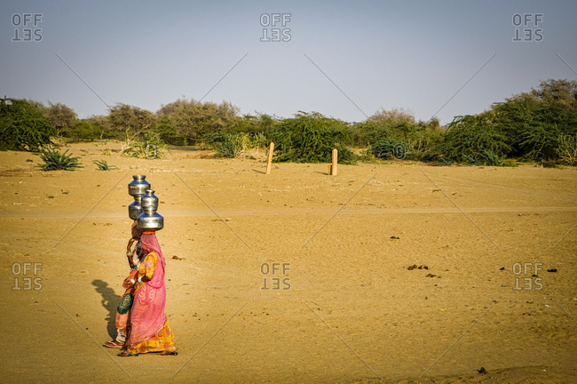 Two women carry water from the well