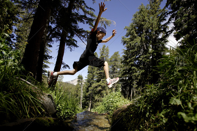 Boy jumping over creek