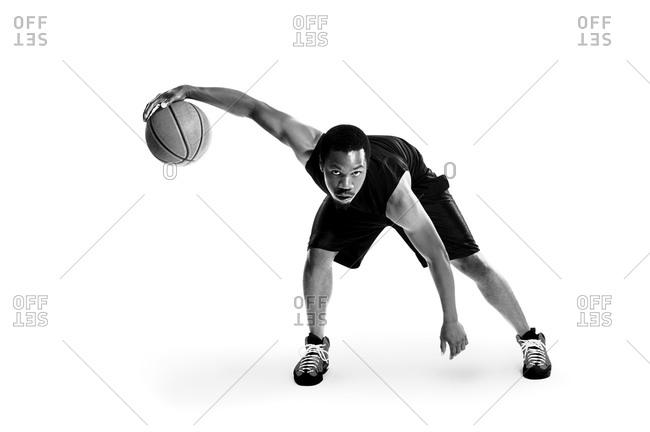 Basketball player dribbling ball studio shot