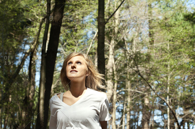 Woman looking up in woods