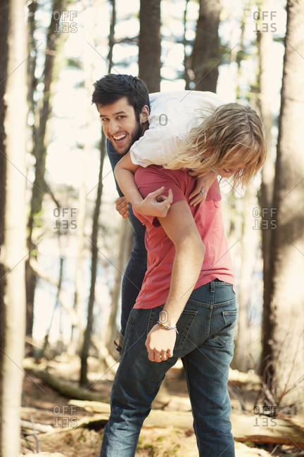 Man holding woman on shoulder in woods