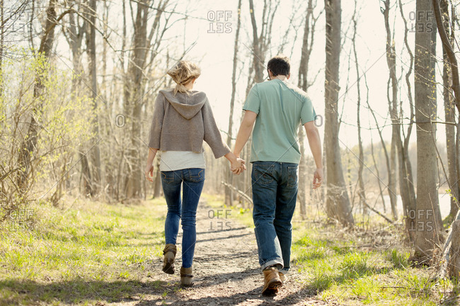 Couple walking through forest path