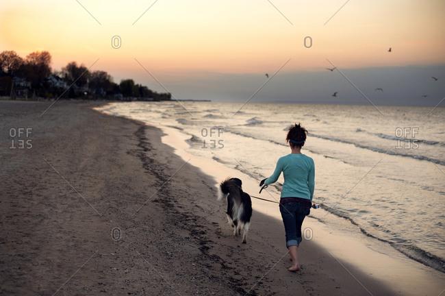 Woman walking dog along beach