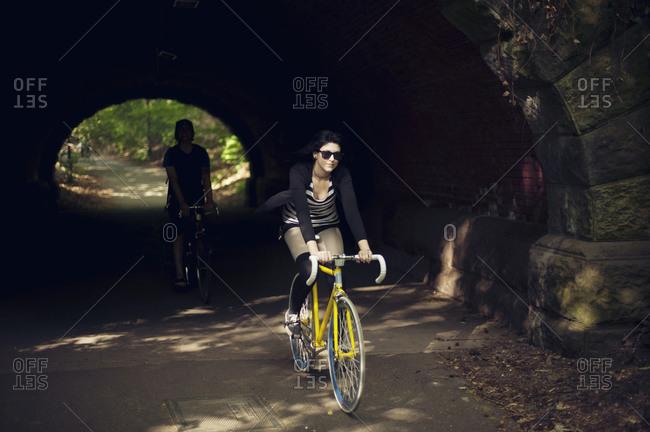 Couple riding bike through tunnel