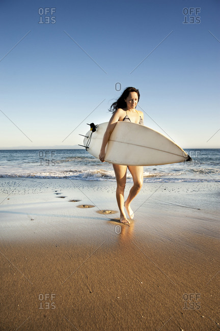 Surfer carrying board out of water