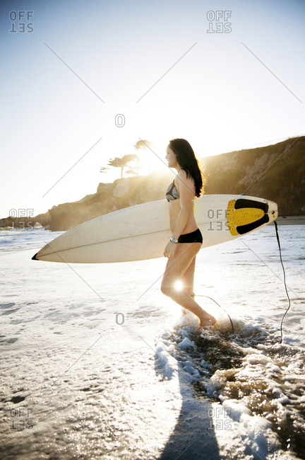 Female surfer walking in water
