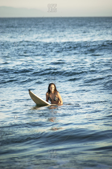 Surfer sitting on board in water