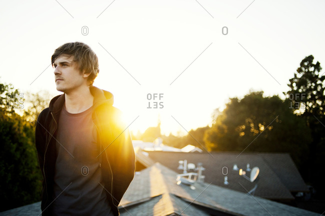 Young man on roof at sunset