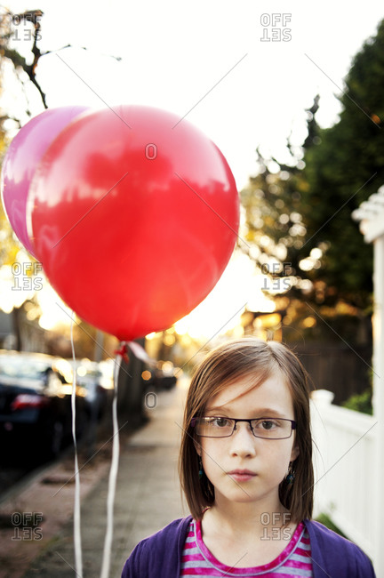 Young girl holding red balloons on sidewalk