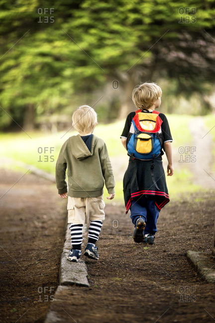Young boy following older boy