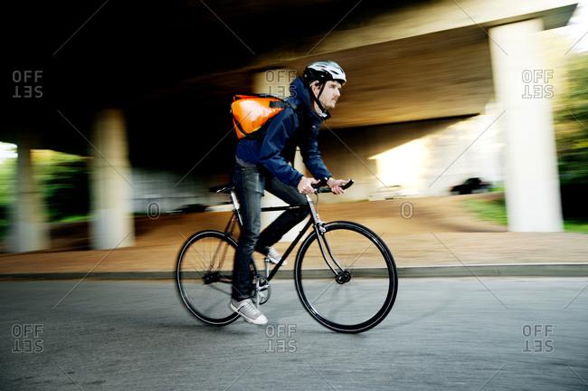 Man biking on road under overpass