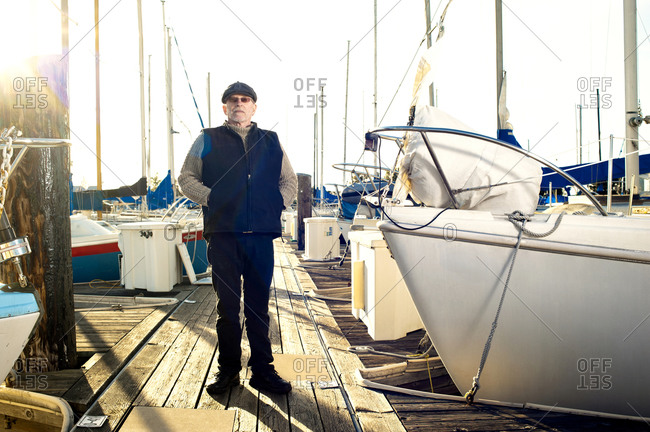 Old man standing on dock with boats