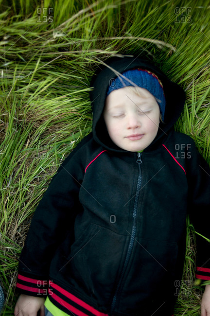 Young boy relaxing in tall grass