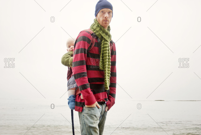 Man with child in backpack on beach