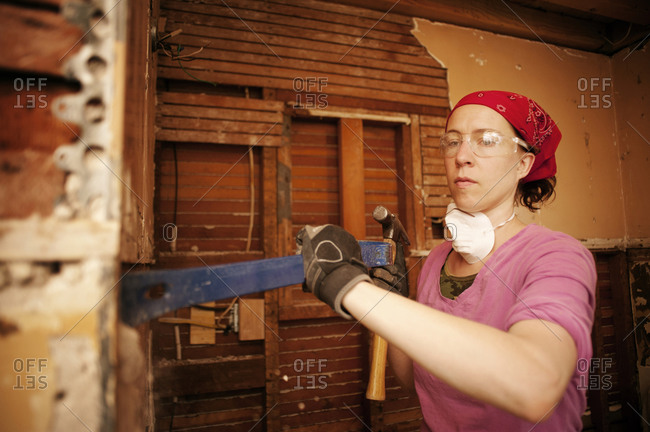Woman renovating home with pry bar